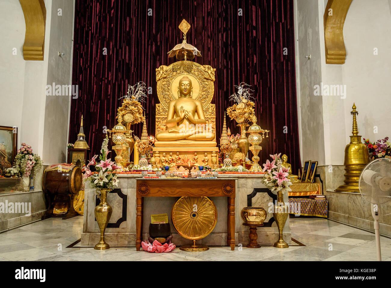 Sitting Golden  Buddha statue at a Buddhist temple at Mulagandhakuti vihara, Sarnath, Varanasi. - Stock Image
