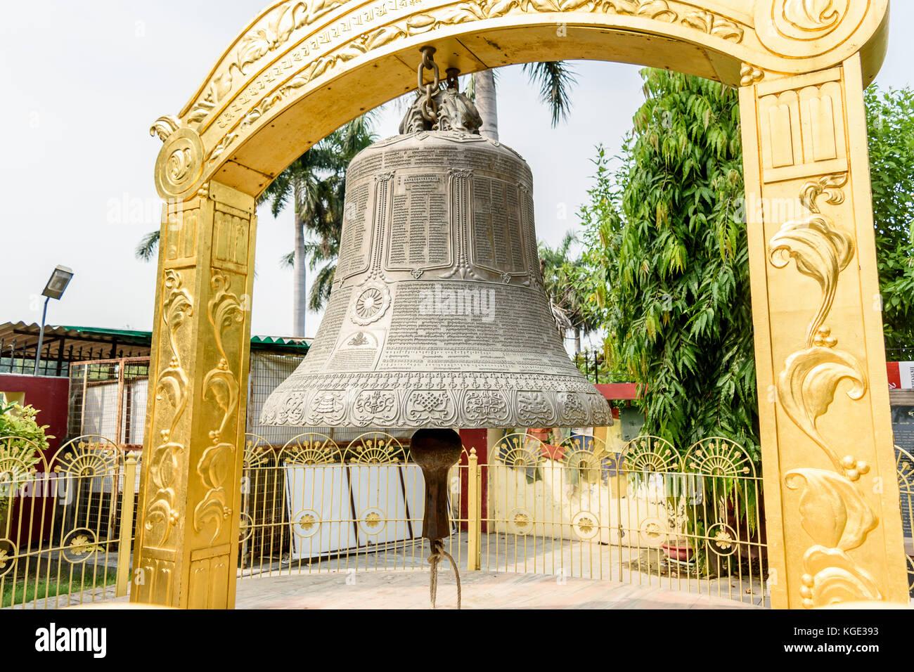 Varanasi, India. Side view of Giant bell with engraved manuscripts at the Buddhist Monastery at Mulagandhakuti vihara - Stock Image