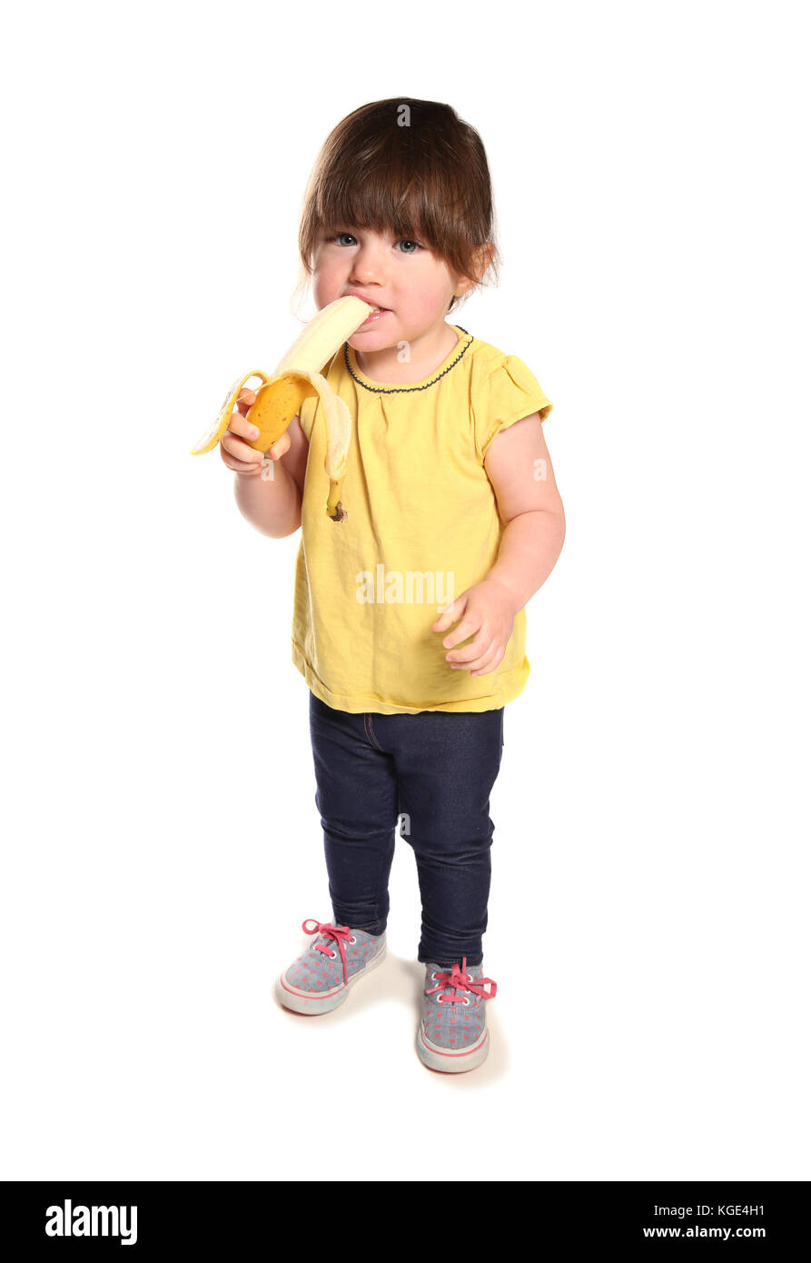 2 year old toddler eating a banana in a studio - Stock Image