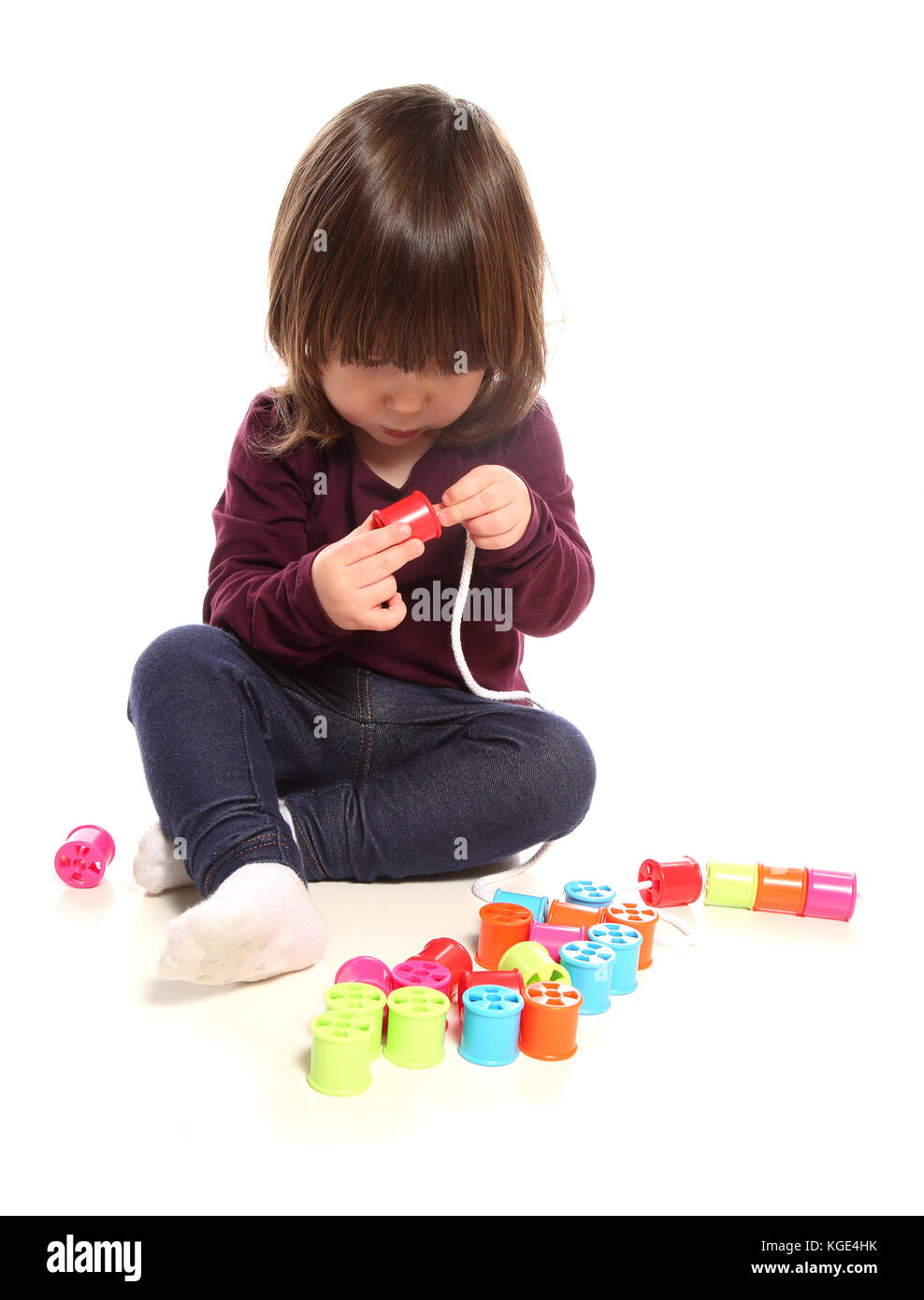 two year old girl playing with cotton reels in studio - Stock Image