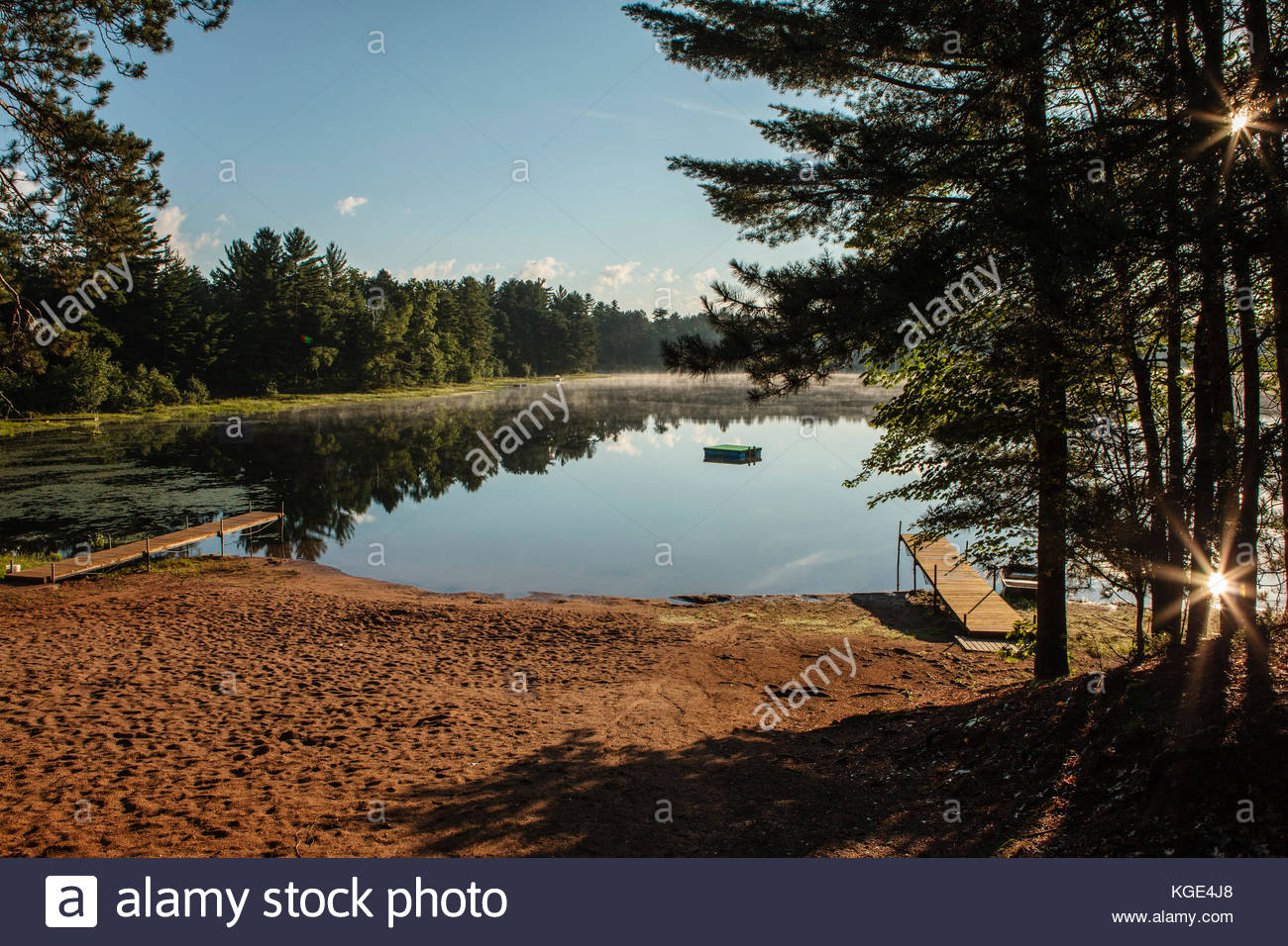 The mid-July early morning cooler air creates a light fog over Patricia Lake in northern Wisconsin, as the sun reflects Stock Photo