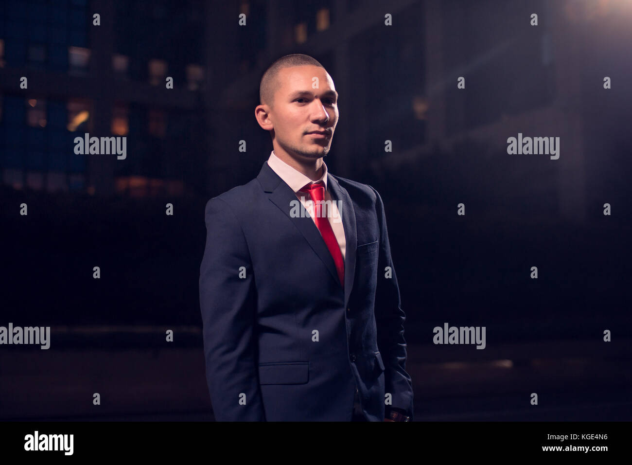 One young adult man, businessman, suit, formal wear, outdoors, night evening dark portrait modern building exterior - Stock Image