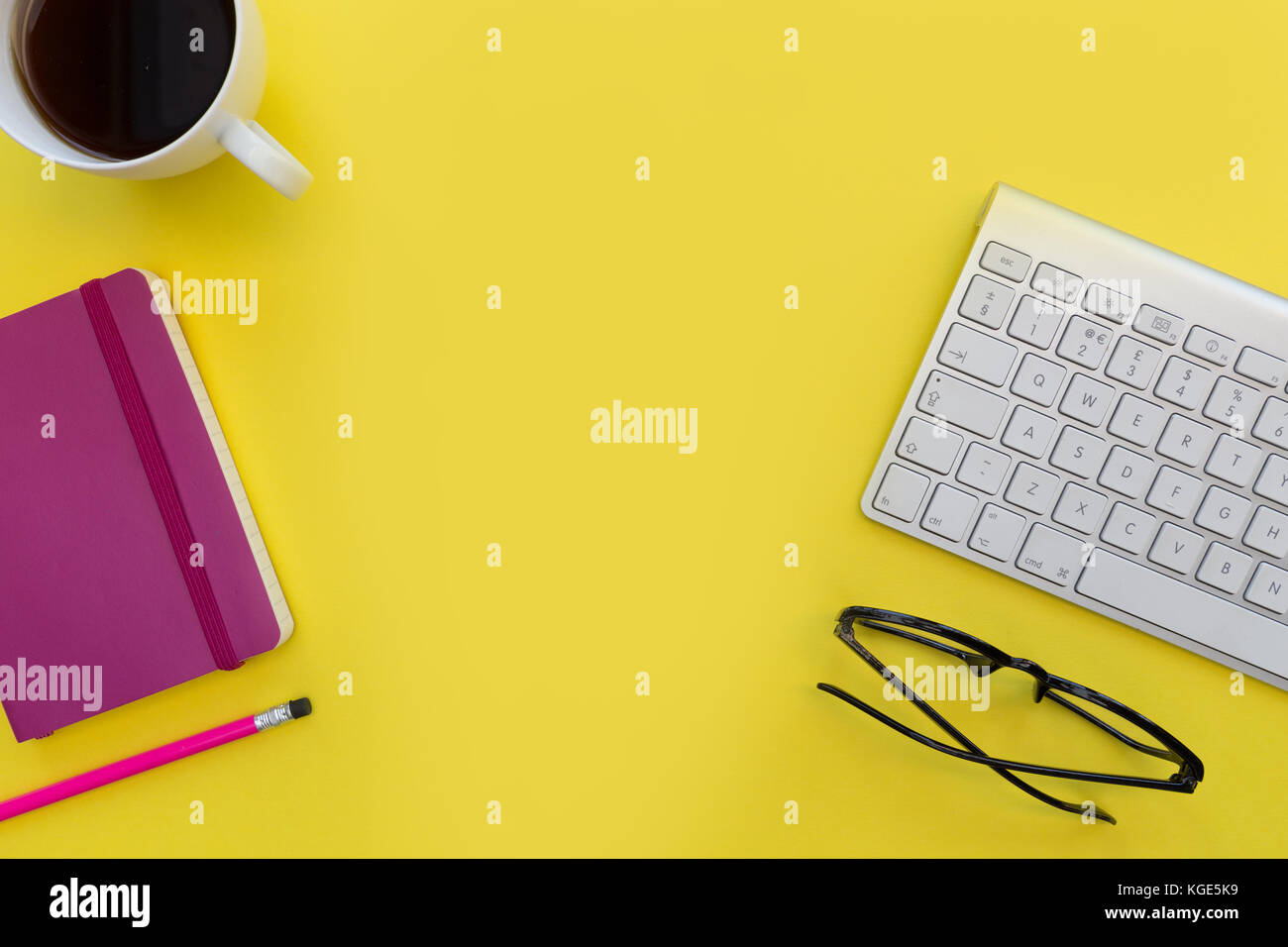 Computer keyboard pink notebook coffee and eyeglesses on bright yellow background - Stock Image