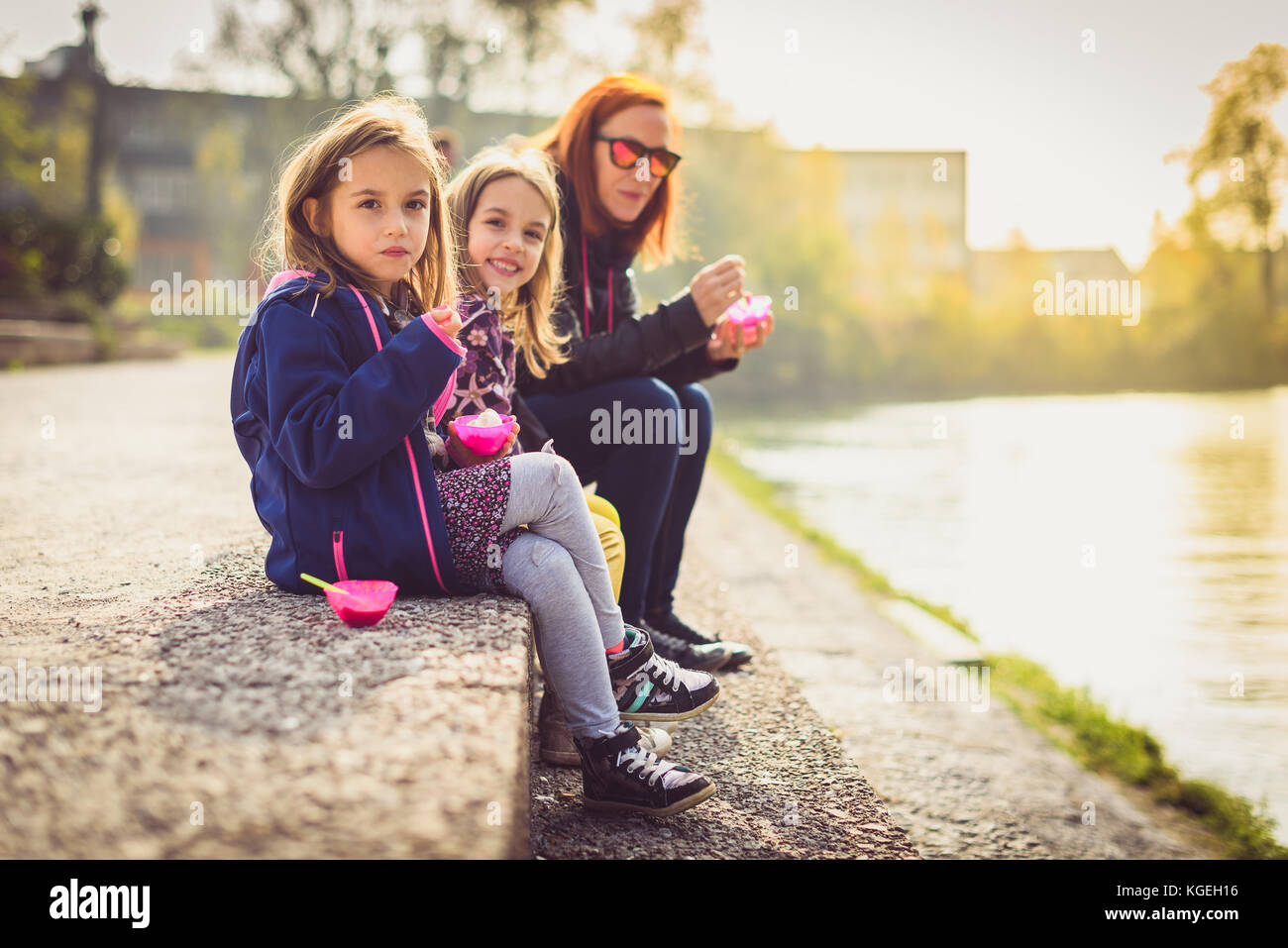 Family eating ice cream, sitting on banks of river Ljubljanica. Mother and twin daughters are sitting next to a - Stock Image