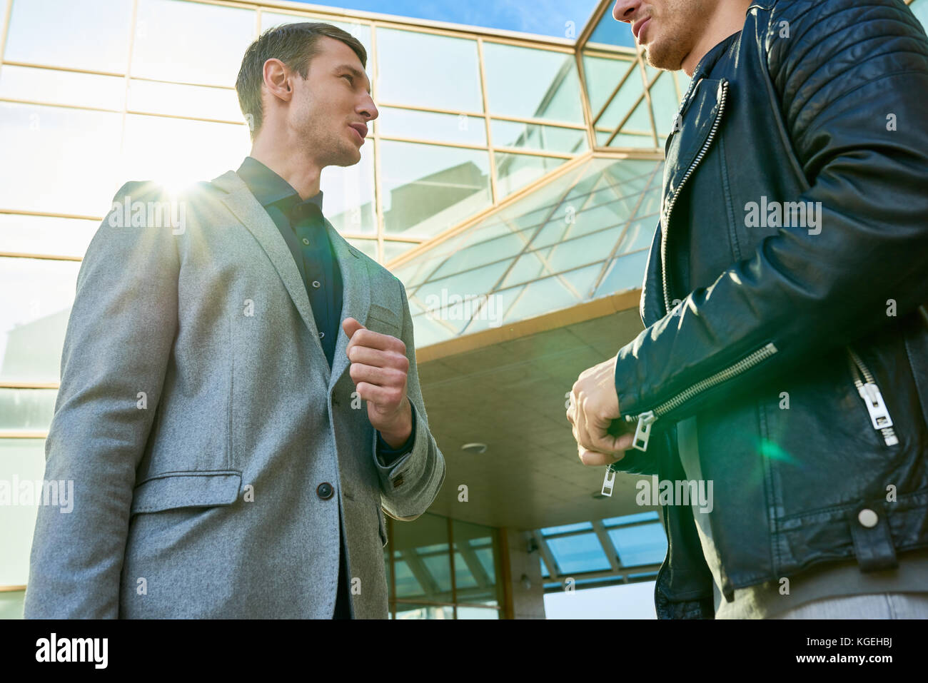 Low angle portrait of two handsome successful men talking outdoors