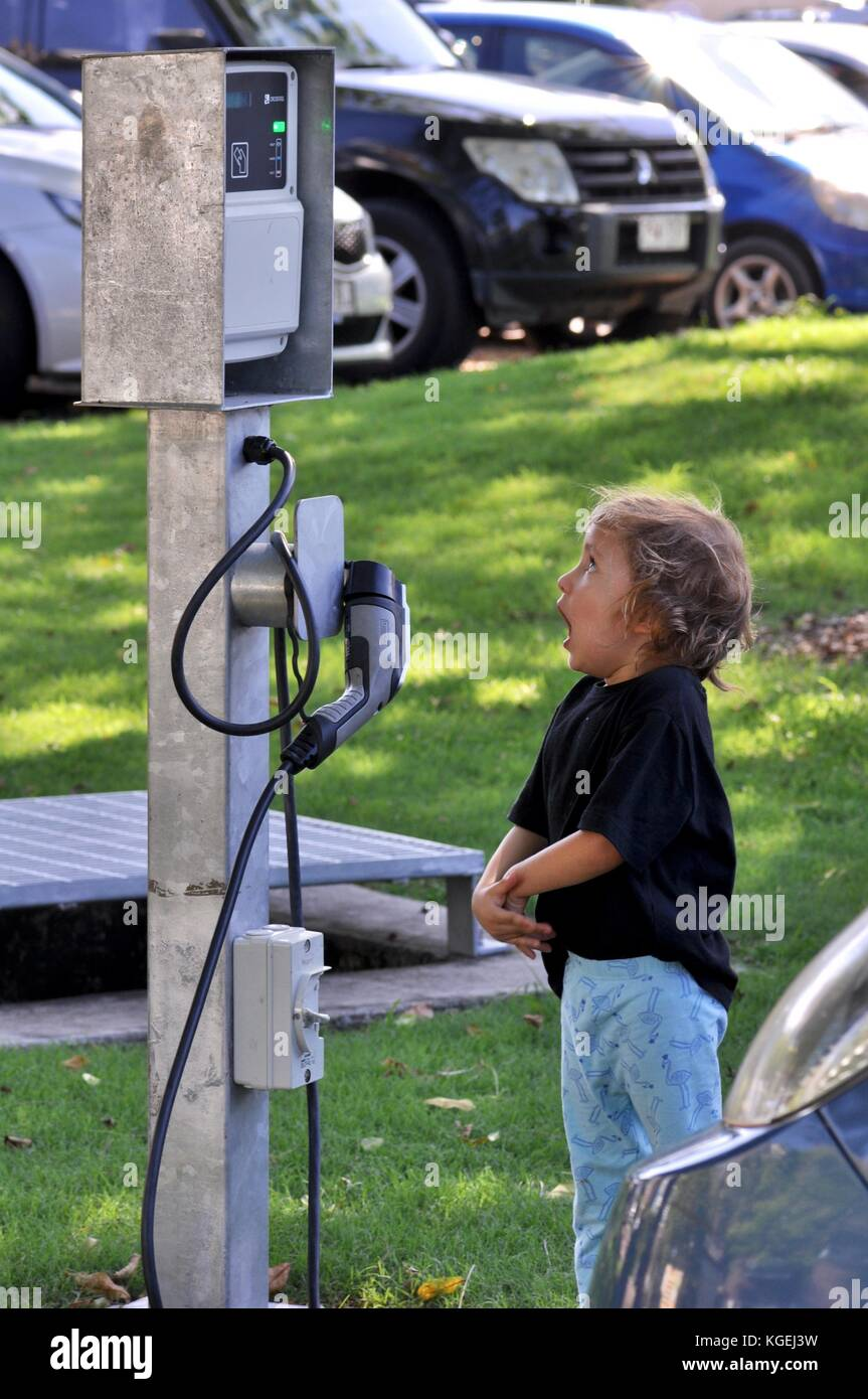 Fear of new technology as a young girl investigates electric car recharge point at Riverway Pool, Townsville, Queensland, - Stock Image