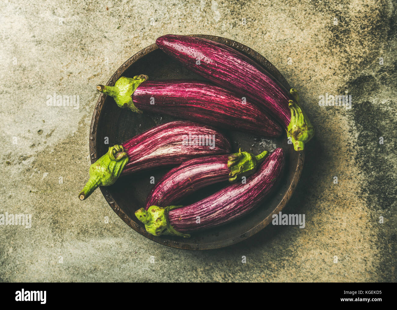 Flat-lay of fresh raw Fall harvest purple eggplants in bowl - Stock Image