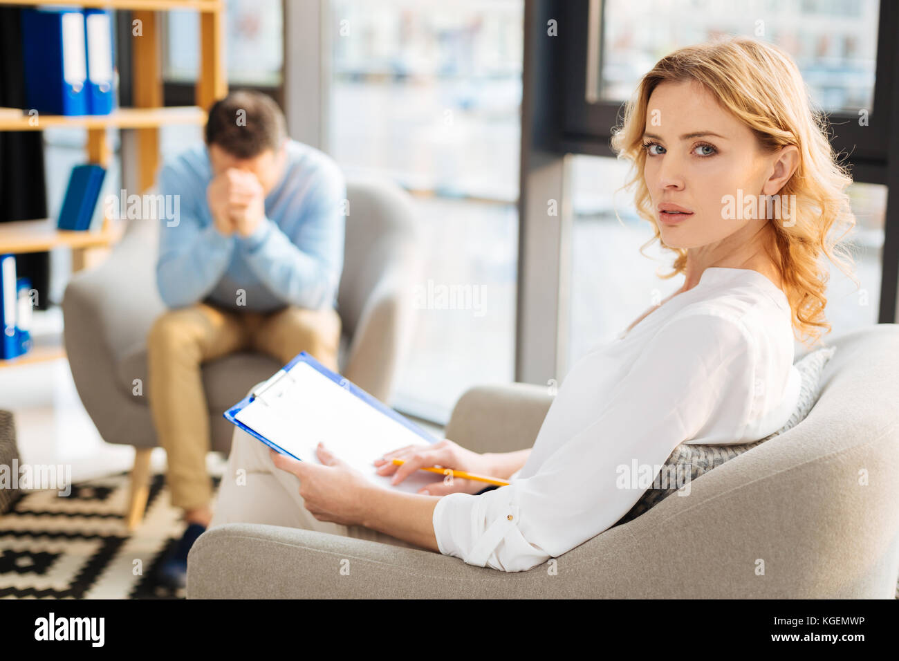 Serious professional therapist holding her notes - Stock Image
