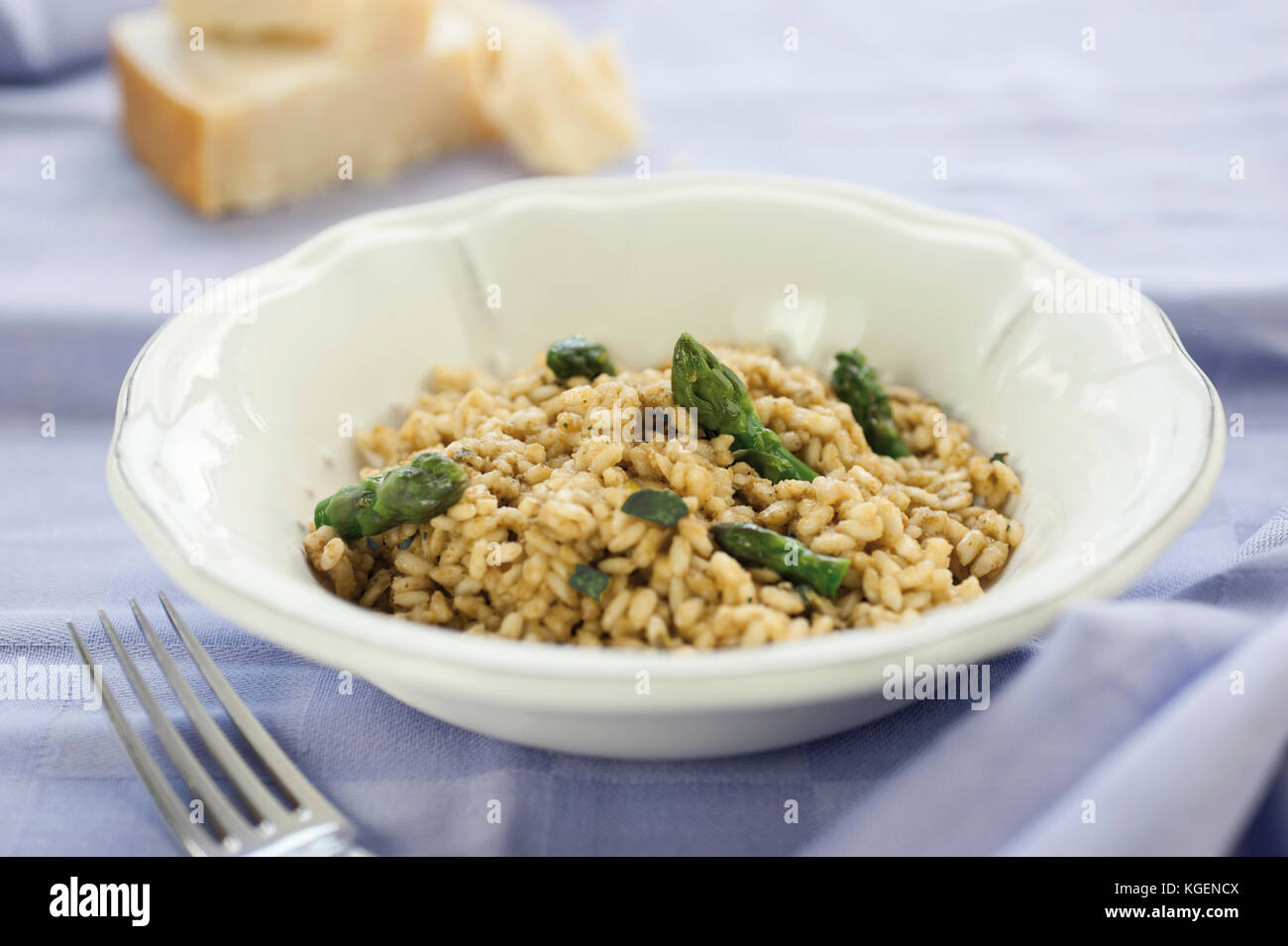 Risotto with Asparagus in ceramic pot on purple tablecloth with a silver fork and pieces of parmesan cheese in the - Stock Image