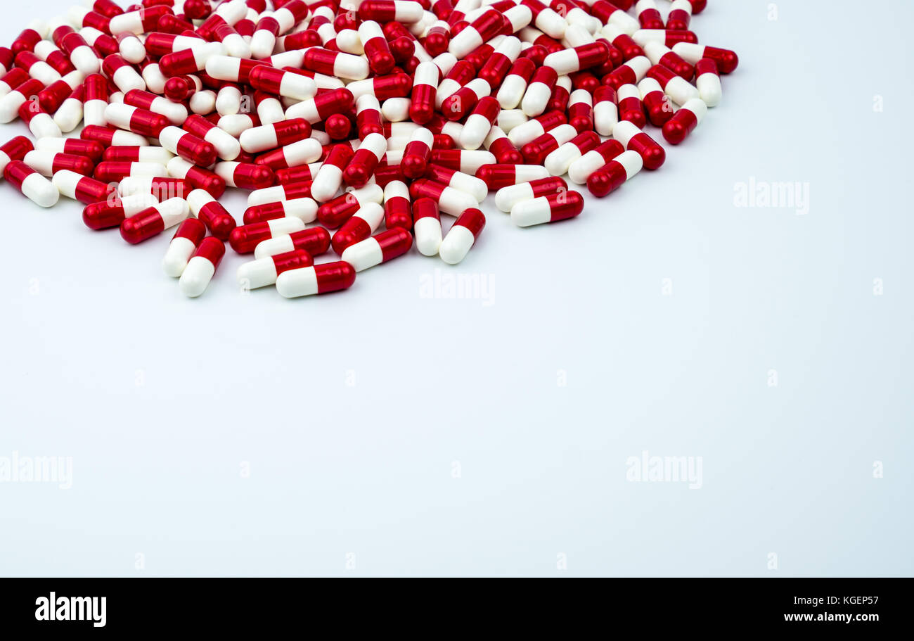 Red, white antibiotic capsules pills on white background with copy space. Drug resistance, antibiotic drug use with - Stock Image