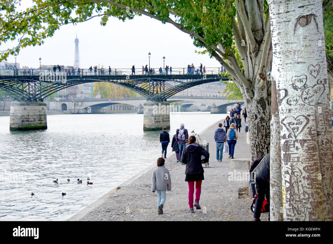 Paris, France. People walking along the north bank of the River Seine, Pont des Arts and Eiffel Tower behind Stock Photo