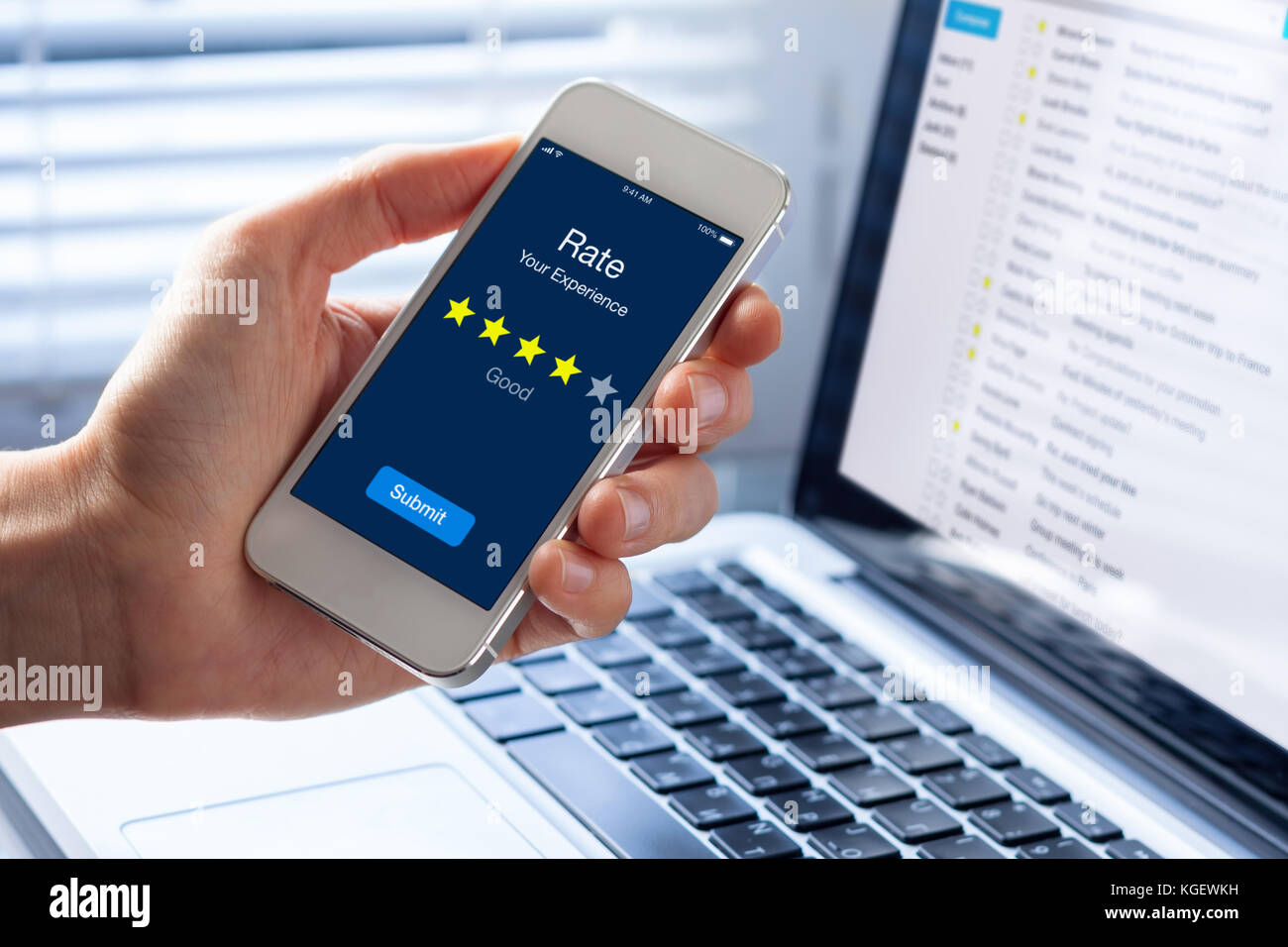 Person rating his experience with 4 stars on smartphone app screen, concept about online customer satisfaction feedback - Stock Image