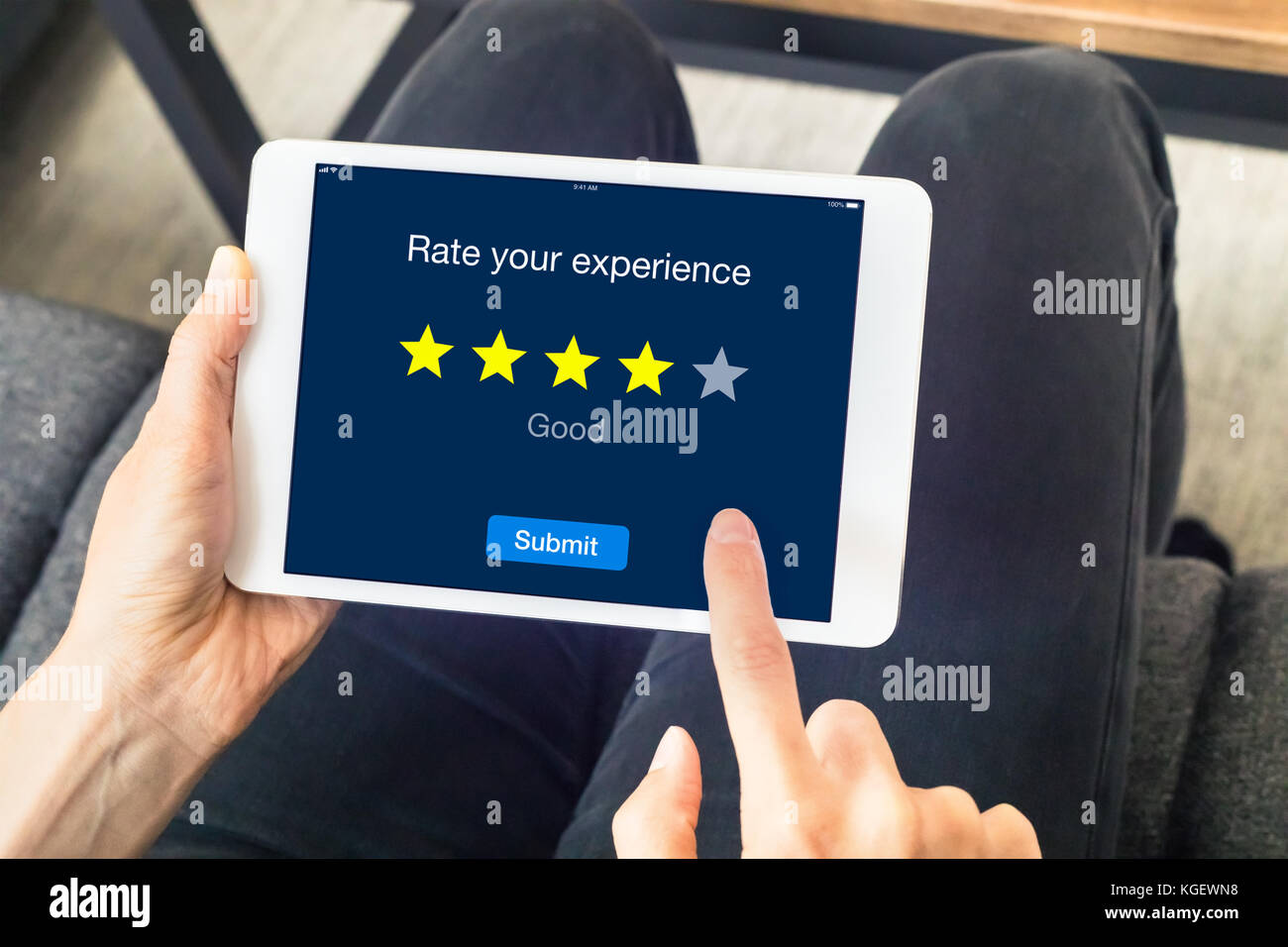 Person using digital tablet computer at home to send customer rating with online website, satisfaction review based - Stock Image