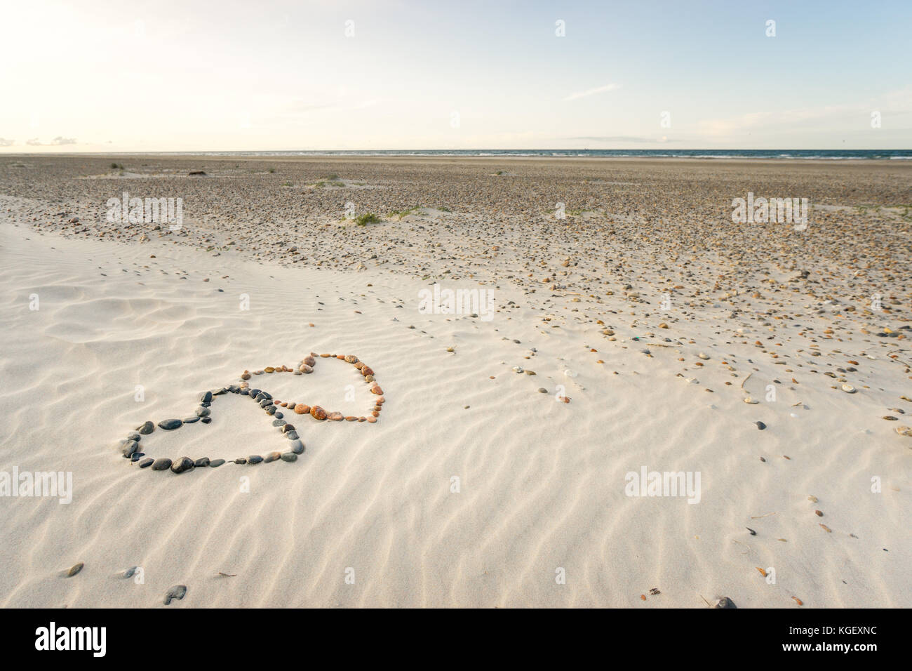 Pebbles arranged in shape of two hearts on sand beach ripples Stock Photo