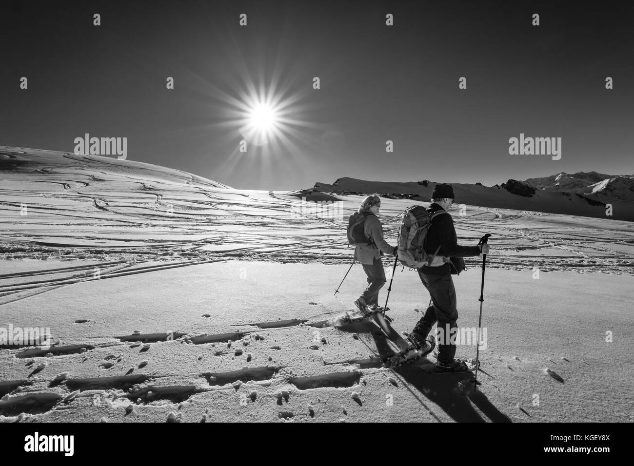 Senior couple is snowshoe hiking through alpine winter mountains at sunset. Bavaria, Germany. - Stock Image