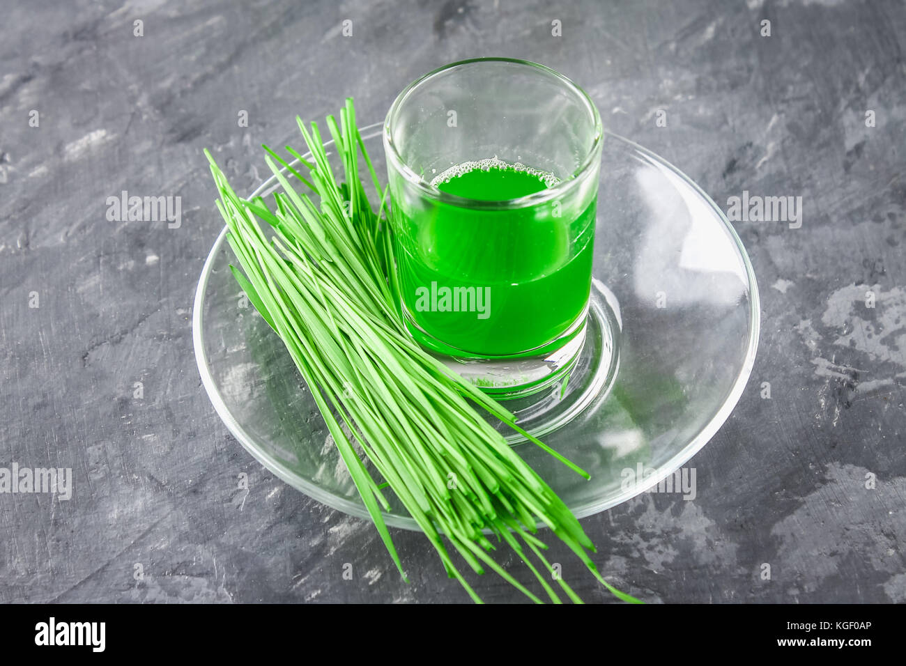 Wheatgrass shot. Juice from wheat grass. Trend of health - Stock Image