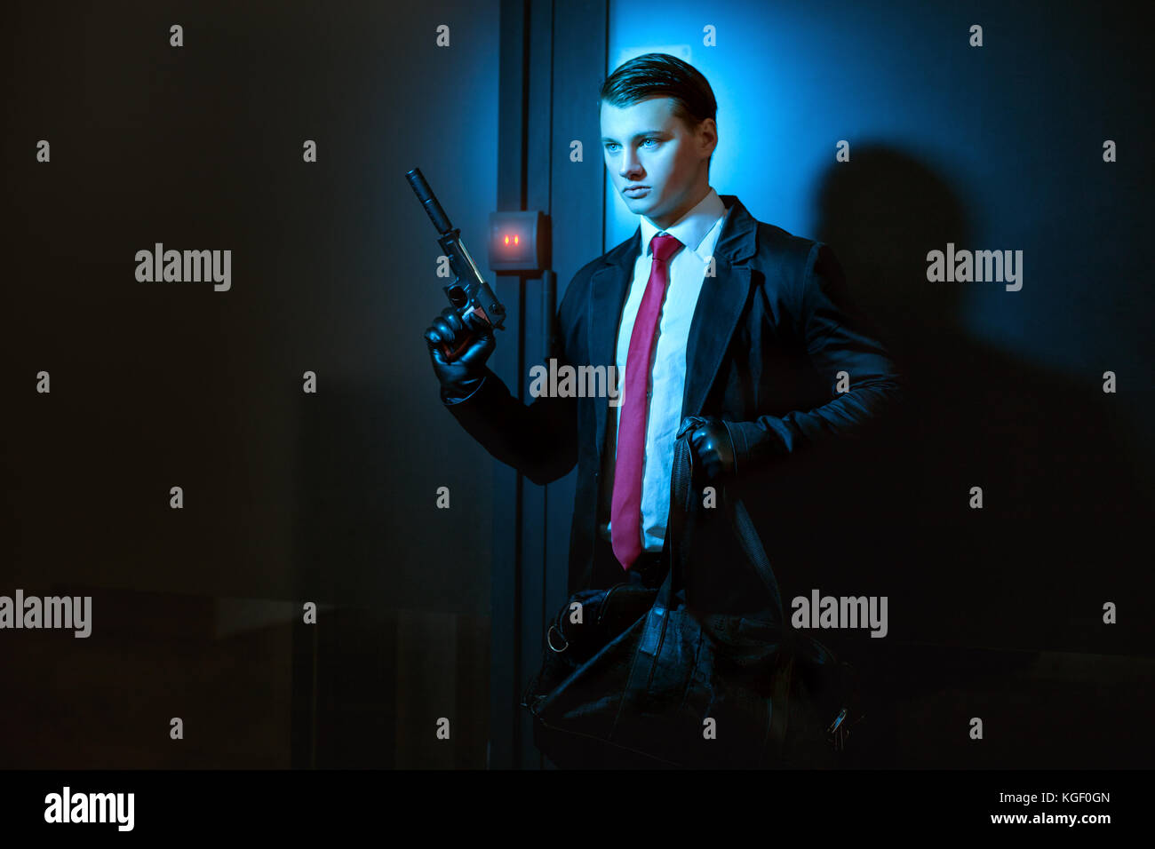 Professional man is a murderer, in his hand a pistol with a silencer. - Stock Image