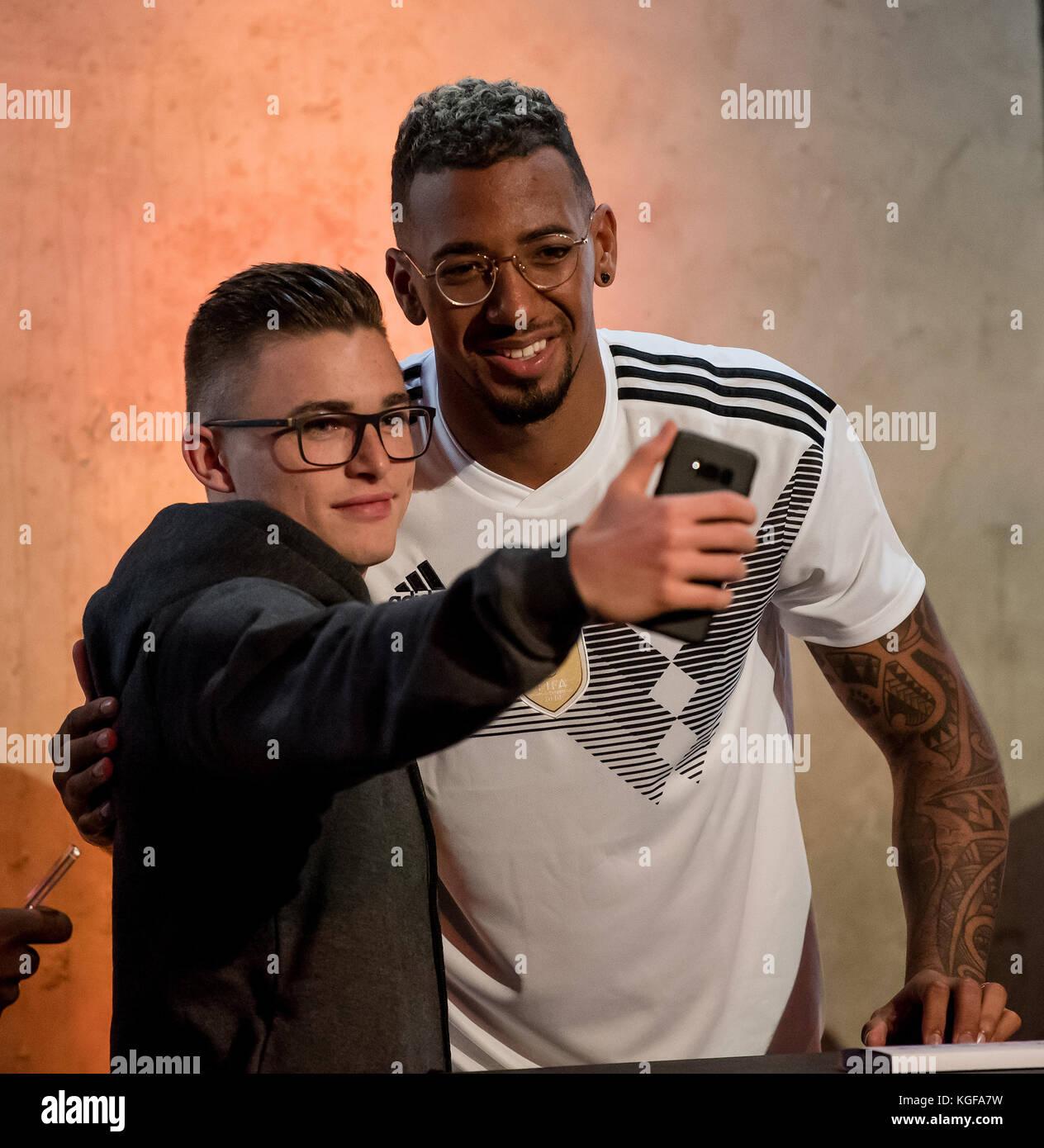 Jerome Boateng laesst sich after der Vorstellung der neuen adidas-Trikots with einem Fan fotografieren  Am heutigen - Stock Image