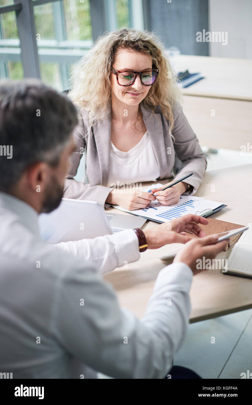 Attractive middle-aged white collar worker in eyeglasses sitting at desk in modern open plan office and analyzing - Stock Image