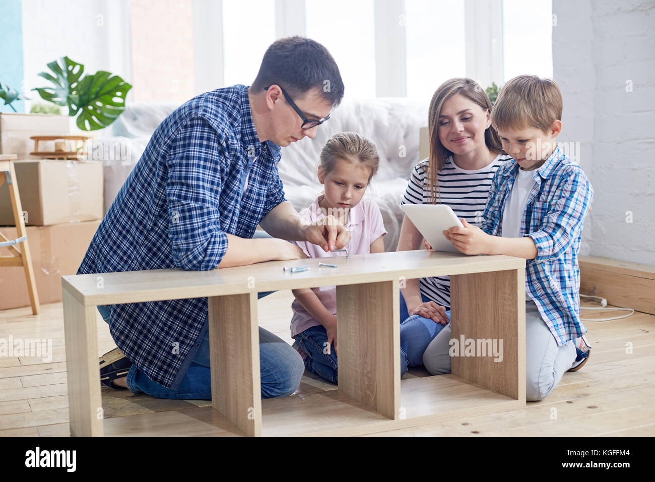 Loving young family of four gathered together at living room of new apartment and wrapped up in assembling wardrobe, Stock Photo