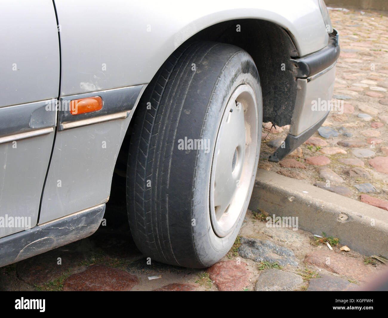 LIEPAJA, LATVIA - AUGUST 25, 2015: Car with worn tire tread on front wheel is parked on the parking place. - Stock Image