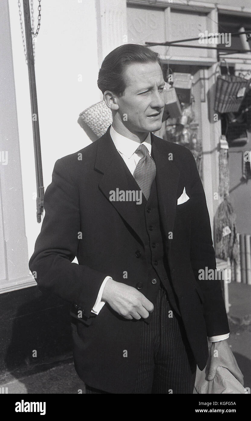 1955, England, a dapper, well-dressed British man standing outside wearing a three-piece suit. - Stock Image