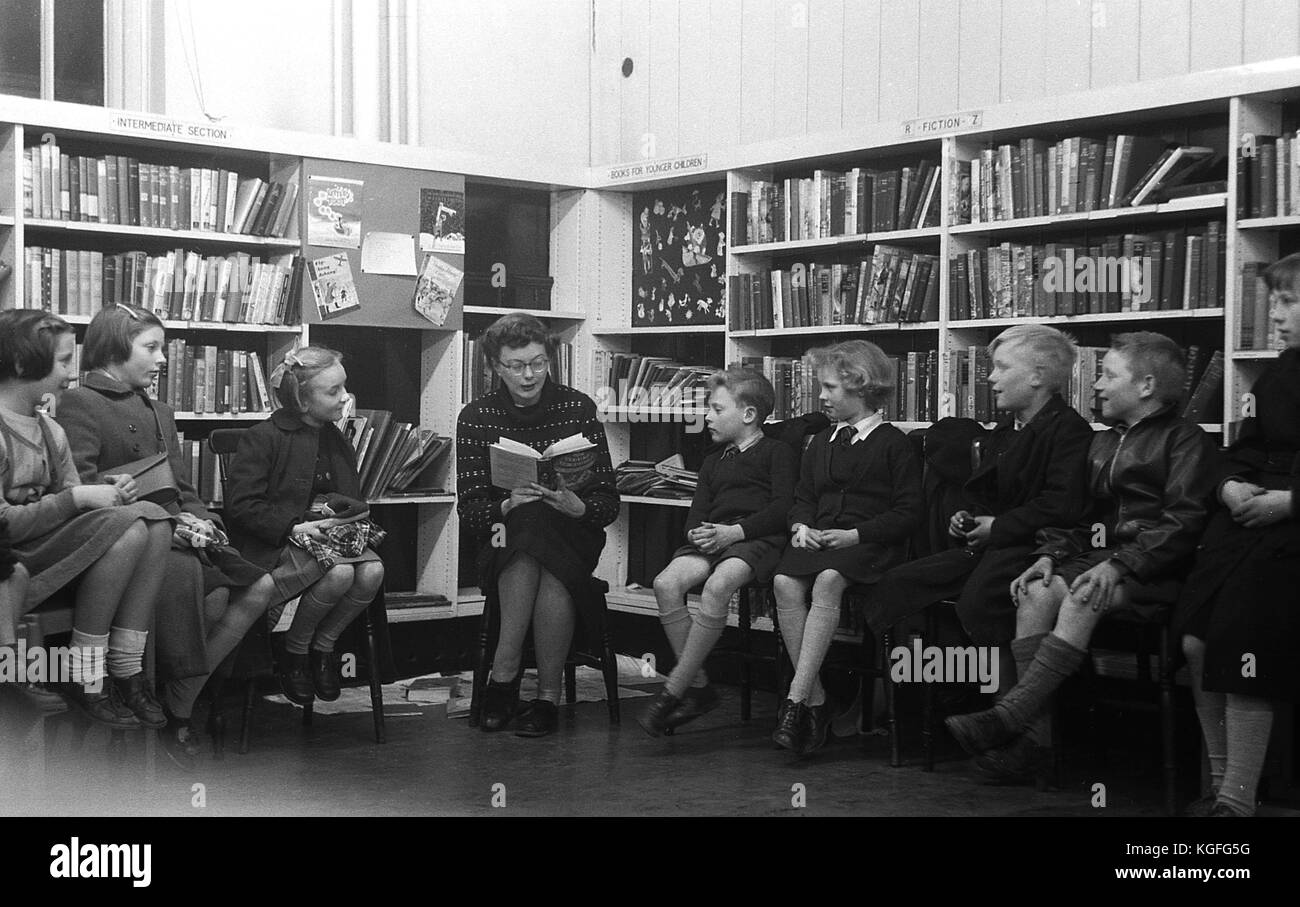 1955, historical picture shows a female teacher sitting and reading a story to a small group of young children in - Stock Image