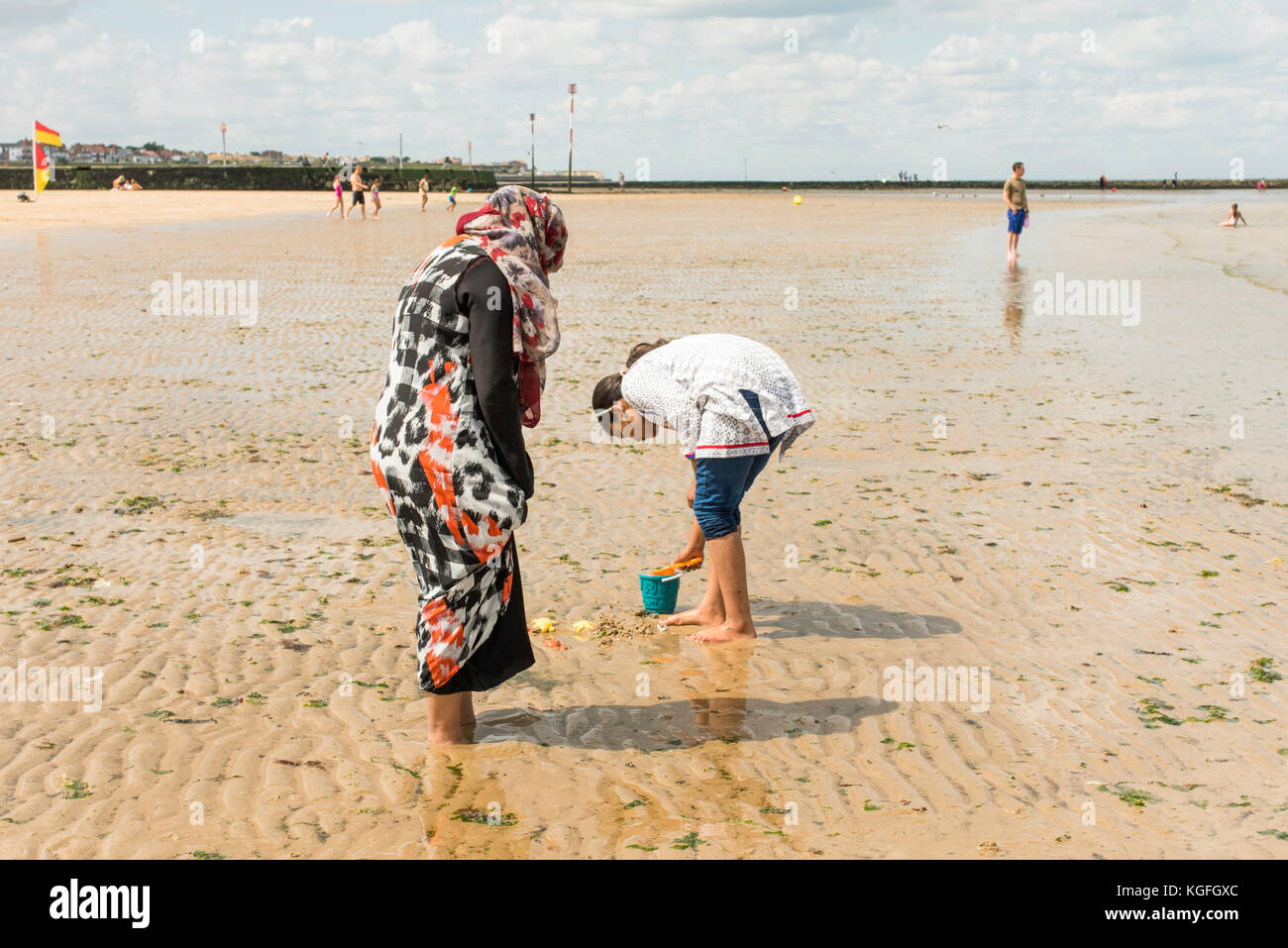 Asian families enjoying a day on the beach at Margate, Kent. - Stock Image
