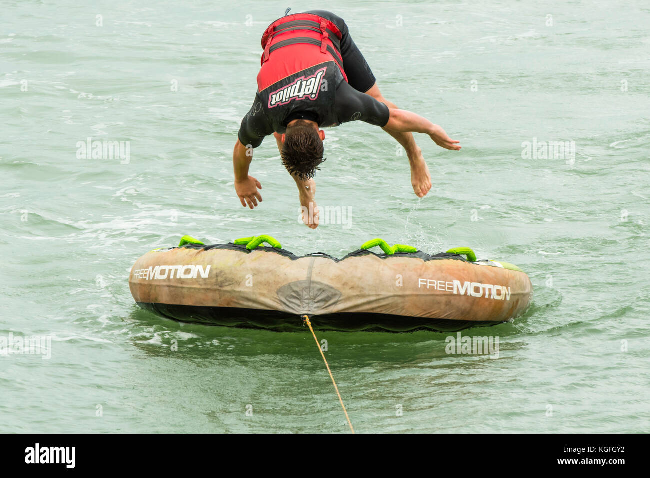 Horizontal close-up of a caucasian man about to back flip on an inflatable donut whilst tubing in the sea. - Stock Image