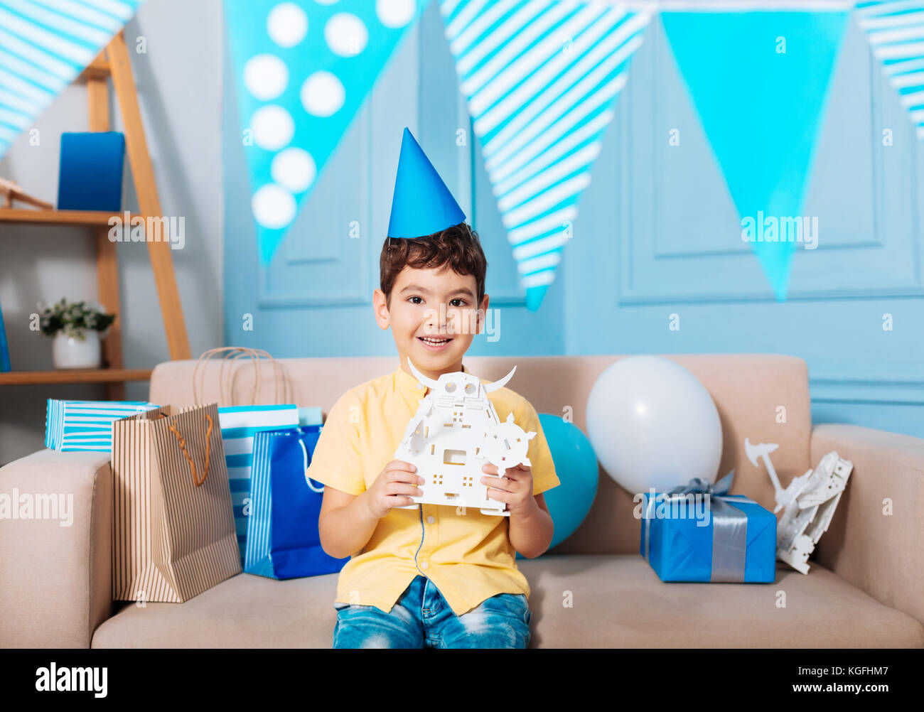 Adorable boy showing his birthday gift - Stock Image