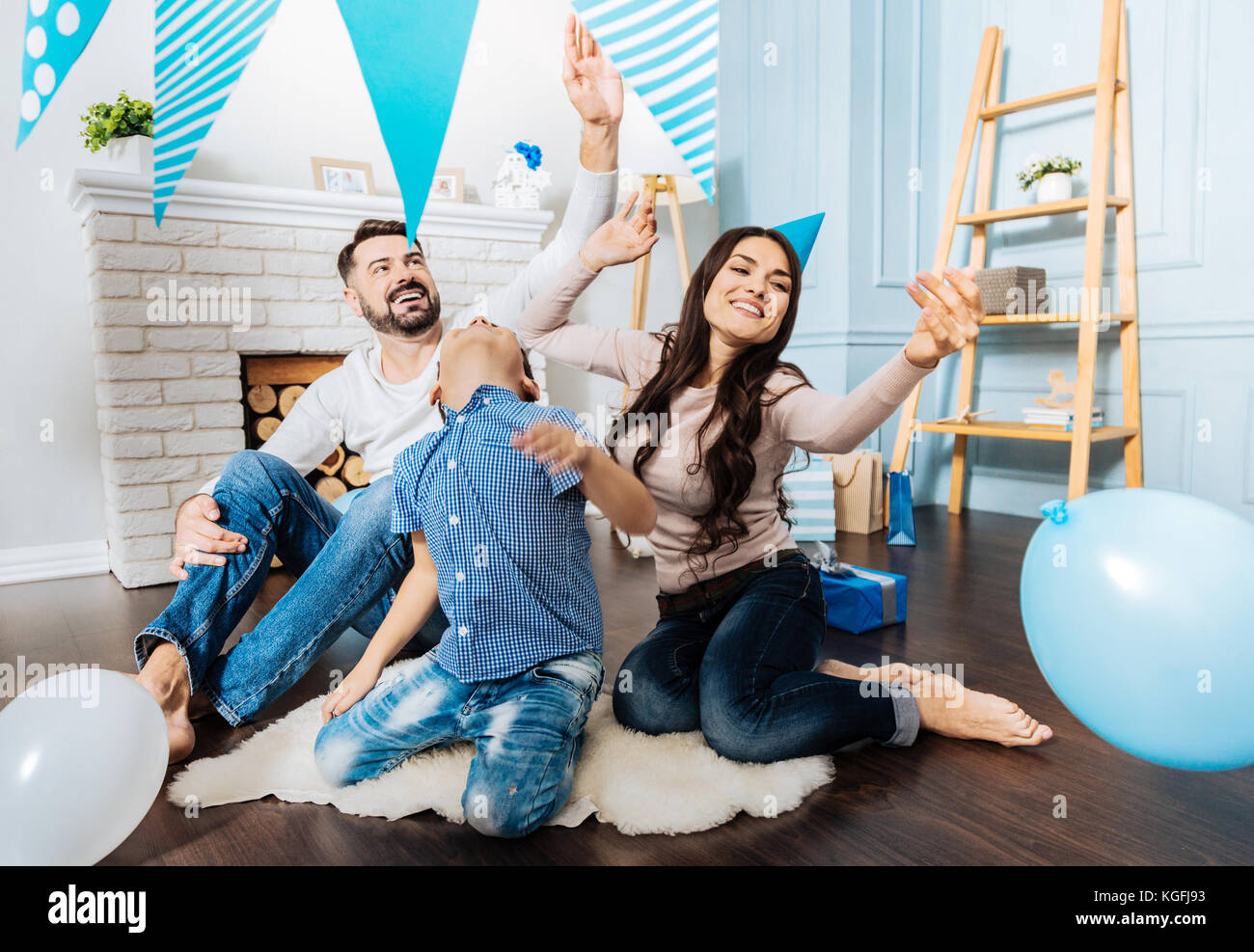 Cheerful family playing with balloons in the living room Stock Photo