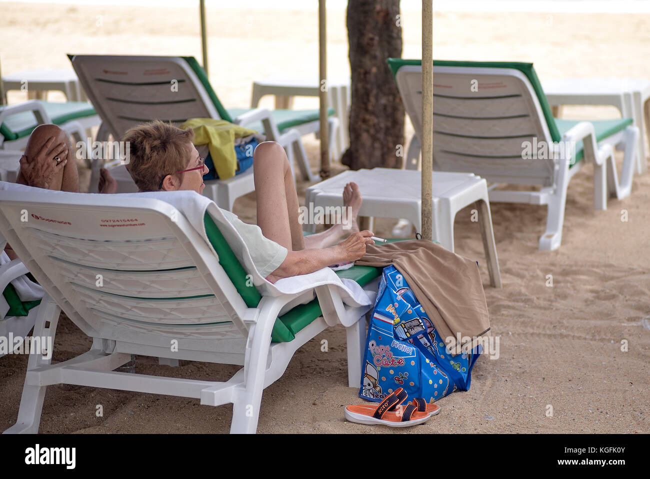 Woman smoking a cigarette on a Thailand beach. The goverment has recently passed legislation against this imposing - Stock Image