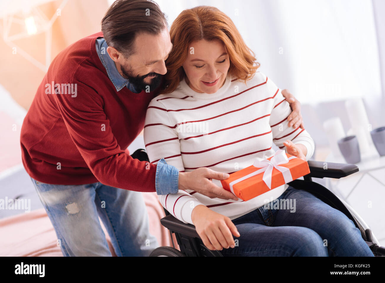 Smiling man giving a present to a crippled woman - Stock Image