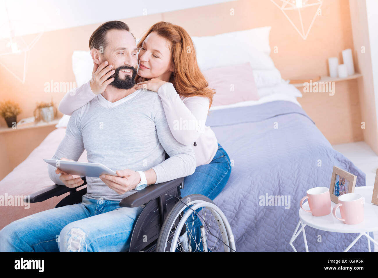 Inspired woman caressing a crippled man - Stock Image