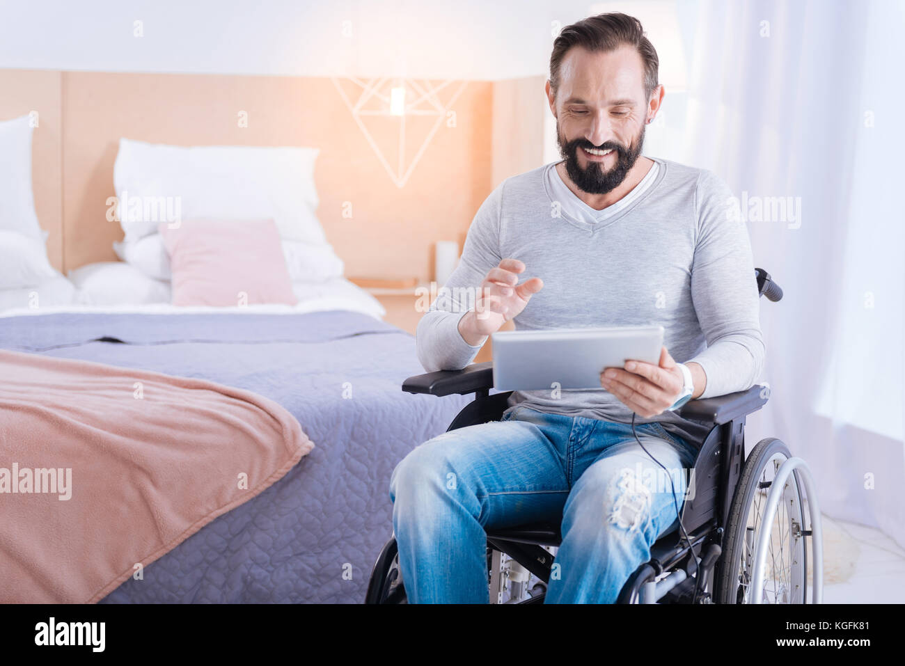 Smiling crippled man using a tablet - Stock Image