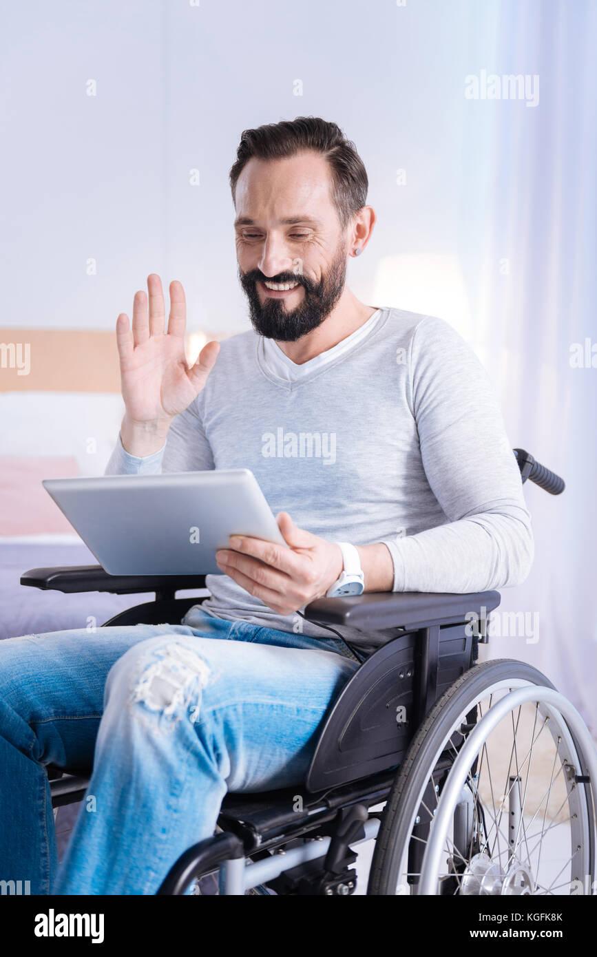 Joyful crippled man waving at the screen - Stock Image