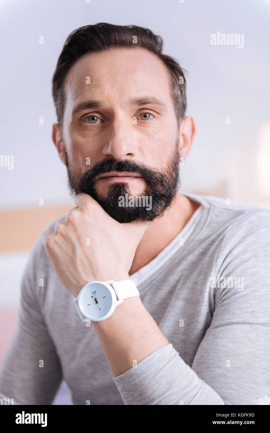 Serious handsome man touching his chin - Stock Image