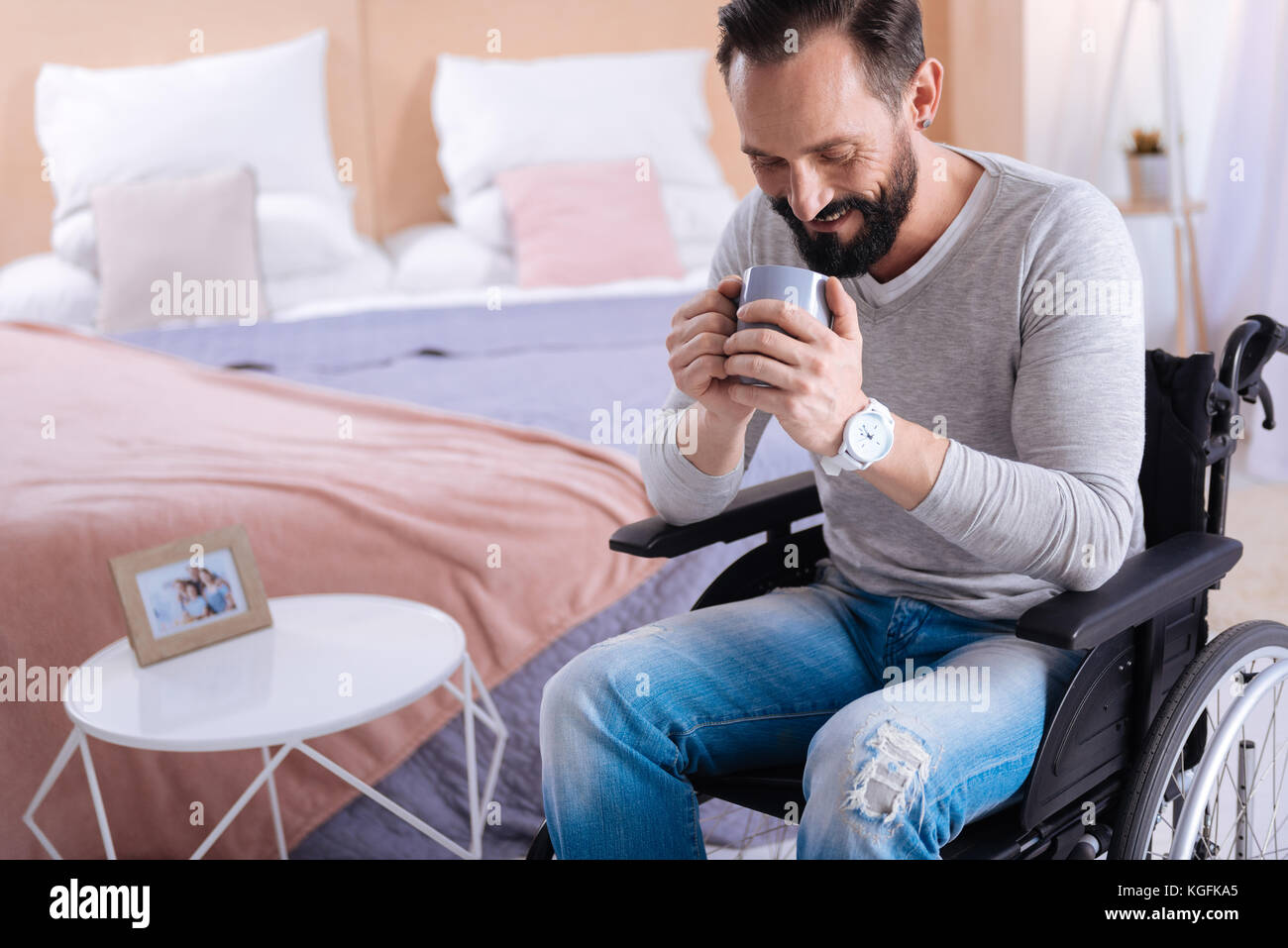 Joyful disabled man holding a cup - Stock Image
