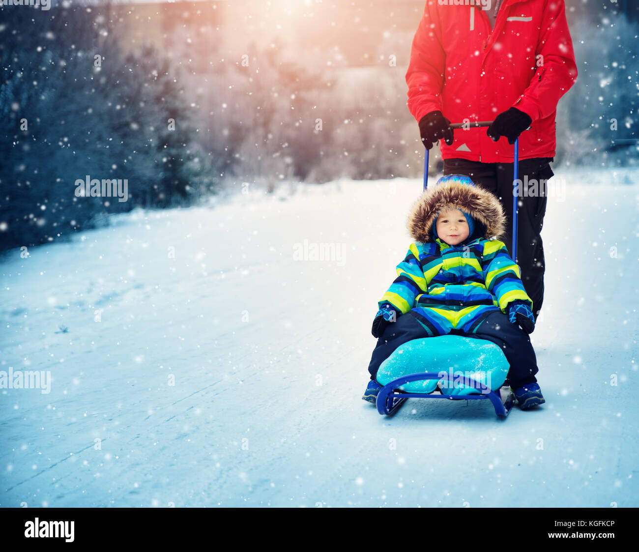Father with sons walking at snowfall - Stock Image