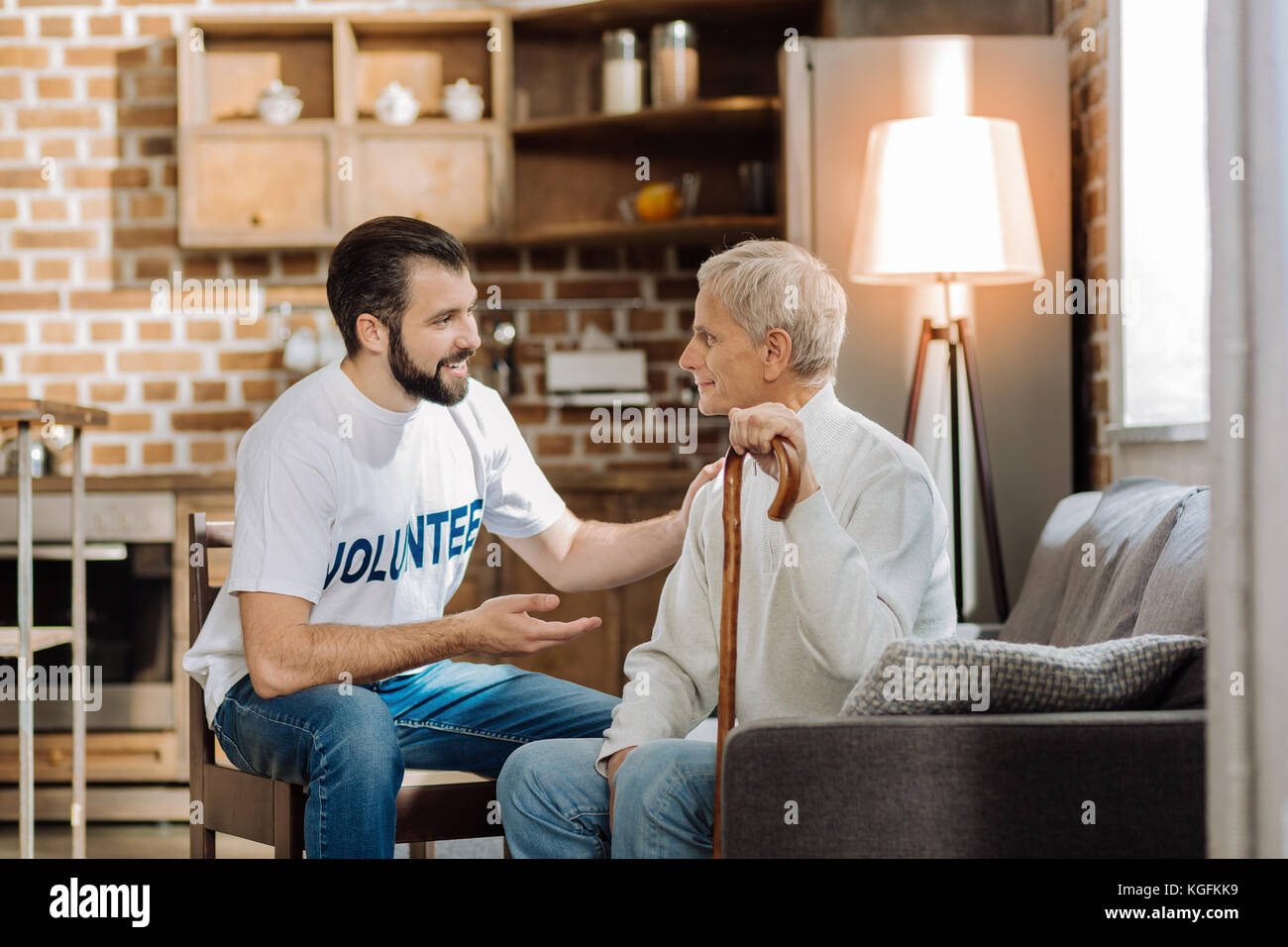 Young attentive volunteer telling the latest new to a senior man - Stock Image