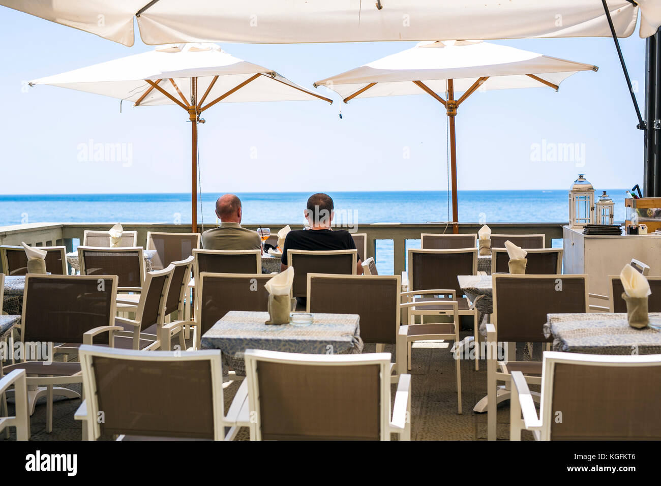 Friends sitting in a bar in font of the méditerranéen ocean looking out. - Stock Image