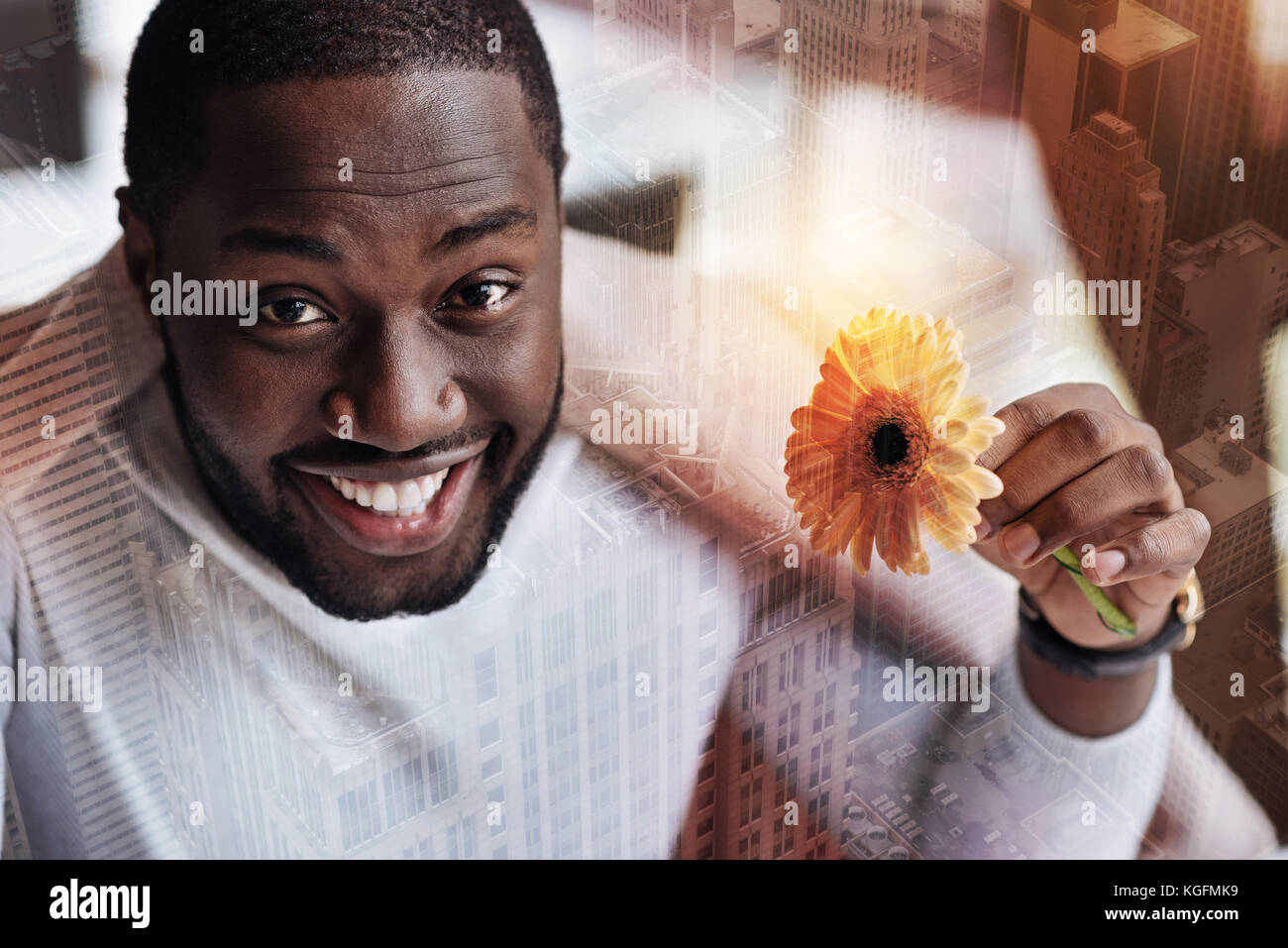 Inspired smiling young man with a flower - Stock Image