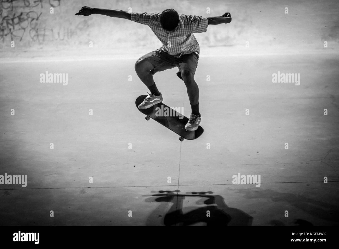 Indian skater doing a trick in a skatepark in Bangalore. - Stock Image