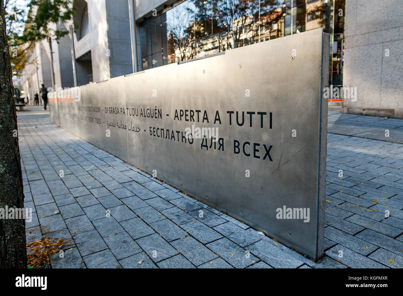 Metal plate on the sidewalk by The Boston Public Library saying 'free to all' in many languages. - Stock Image