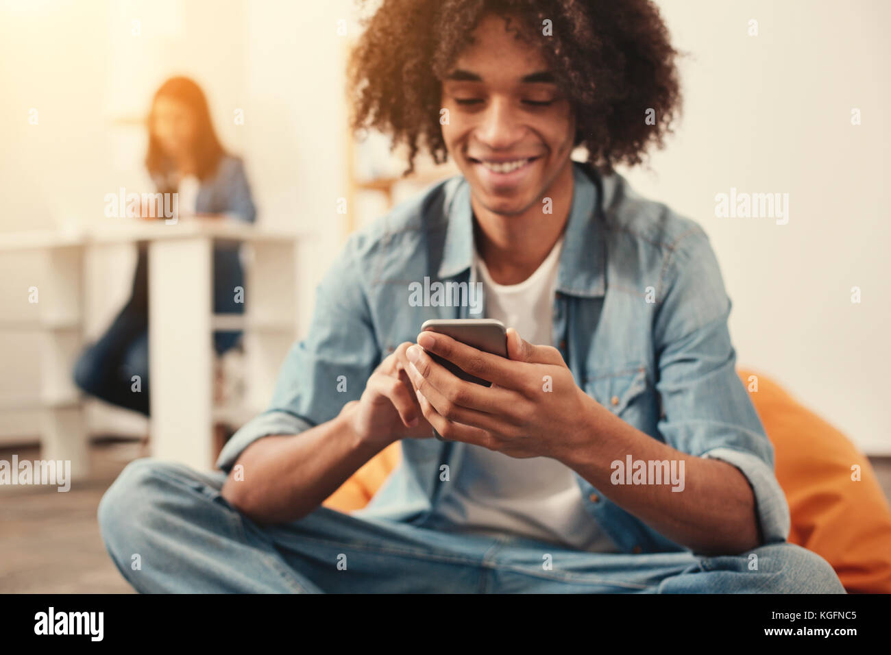 Cheerful student sitting in a comfortable beanbag chair and holding a smartphone - Stock Image