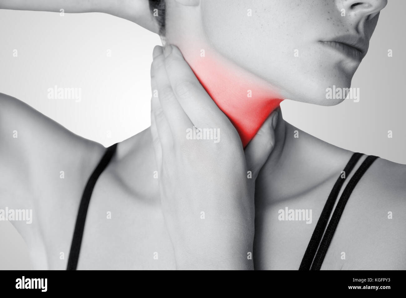 Closeup view of a young woman with pain on neck or thyroid gland on gray background. Black and white photo with - Stock Image