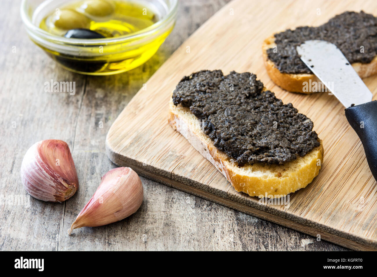 Black olive tapenade with anchovies, garlic and olive oil in toast on wooden table - Stock Image