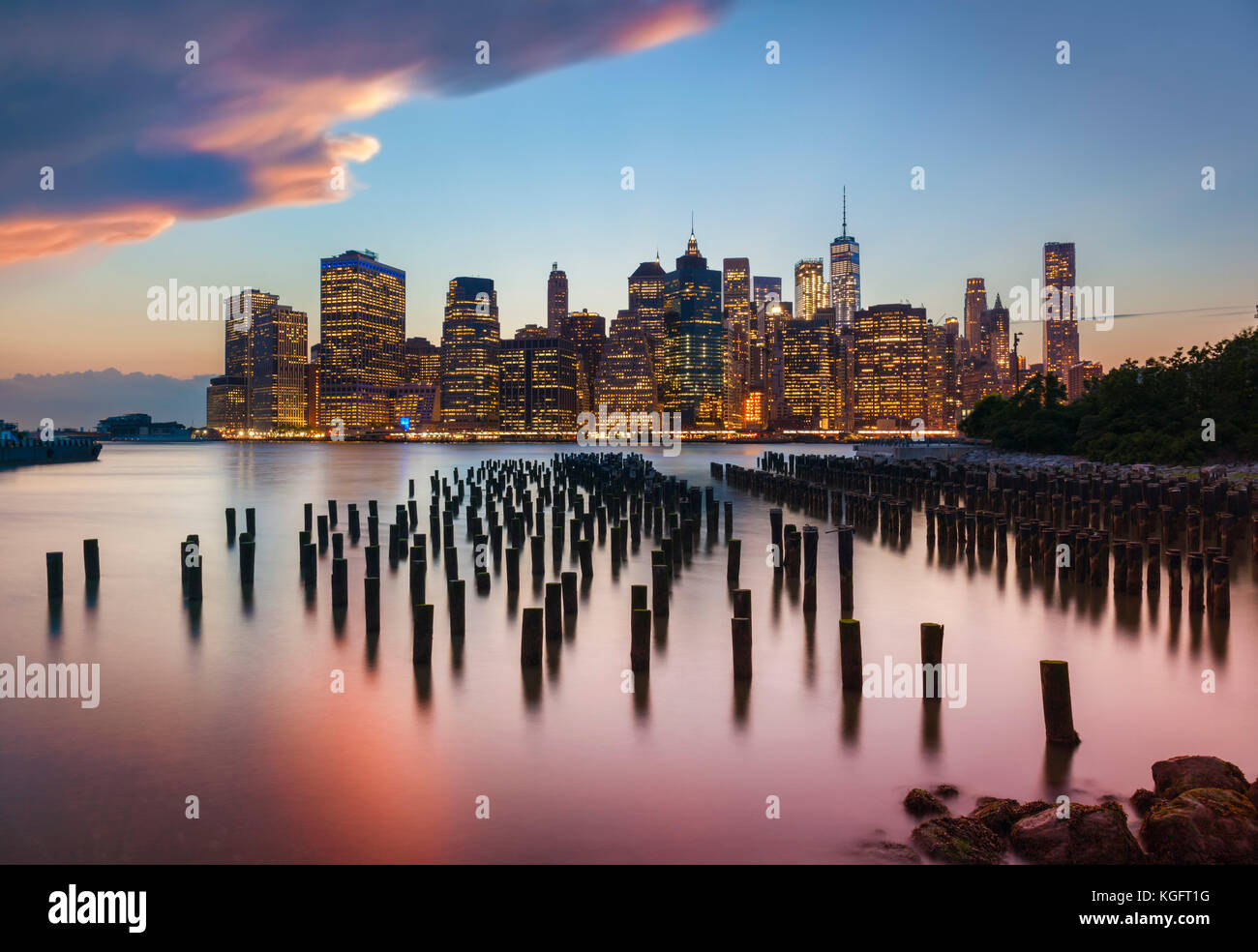 manhattan skyline New York skyline stormy sunset sky above the skyscrapers with Brooklyn old pier 1 wooden pilings - Stock Image