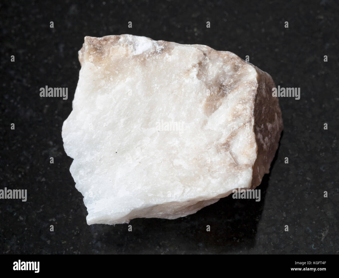 macro shooting of natural mineral rock specimen - raw Anhydrite stone on dark granite background Stock Photo