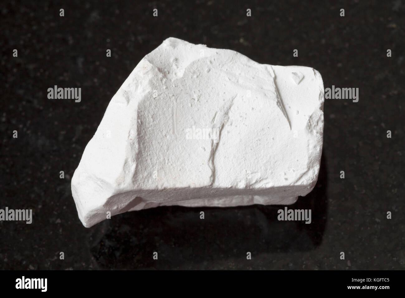 macro shooting of natural mineral rock specimen - raw chalk stone on dark granite background - Stock Image
